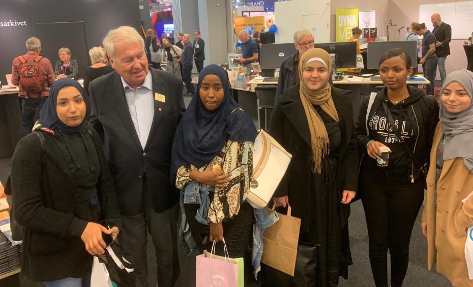 Gamle bokmässegeneralen Bertil Falck tillsammans med Jumana, Zamzam, Ghezel, Segen och Lobna från ekonomiprogrammet; -Vilken entreprenör, tänkte tjejerna!
