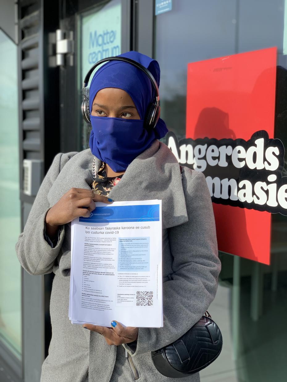 Zamzam Aweys Ali delar ut informationsblad på somaliska för att minska risken att människor inte förstår hur vi skall skydda oss från viruset. Själv bär hon matchande munskydd för att förstärka allvar och skydd på samma gång.
